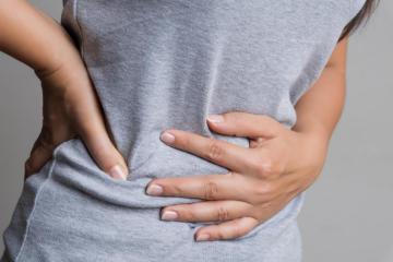 Young woman having painful stomachache. Chronic gastritis. Abdom